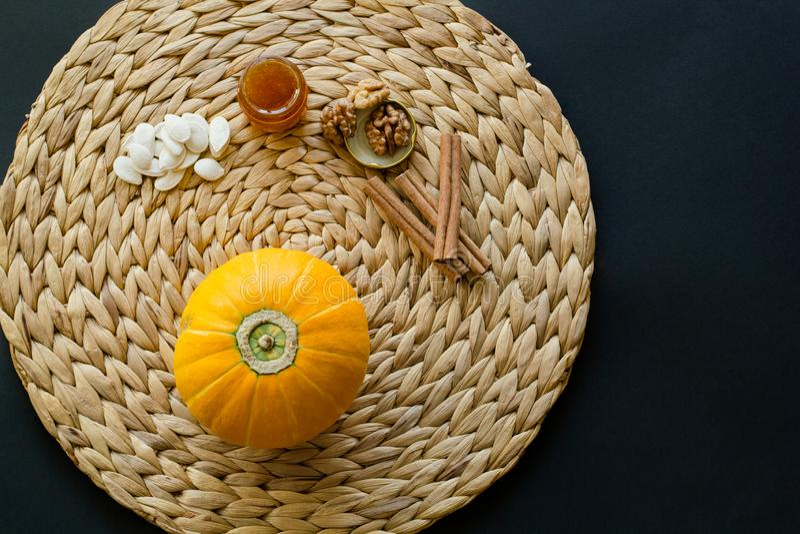 Η μικρή κολοκύθα με τους σπόρους, λίγο γυαλί μπορεί του μελιού, των ξύλων καρυδιάς και των ραβδιών κανέλας σε ένα χαλί/μια πετσέτ στοκ εικόνα με δικαίωμα ελεύθερης χρήσης
