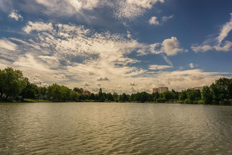 Η μικρή λίμνη σε ένα πάρκο μια νεφελώδη θερινή ημέρα στοκ εικόνα