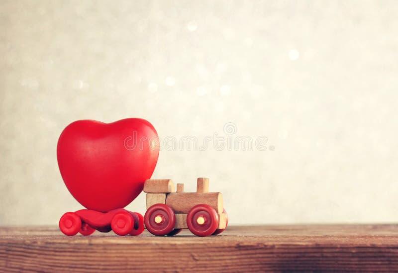 Η μικρή ξύλινη ατμομηχανή παιχνιδιών φέρνει την καρδιά, κάρτα ημέρας βαλεντίνων ` s στοκ φωτογραφία