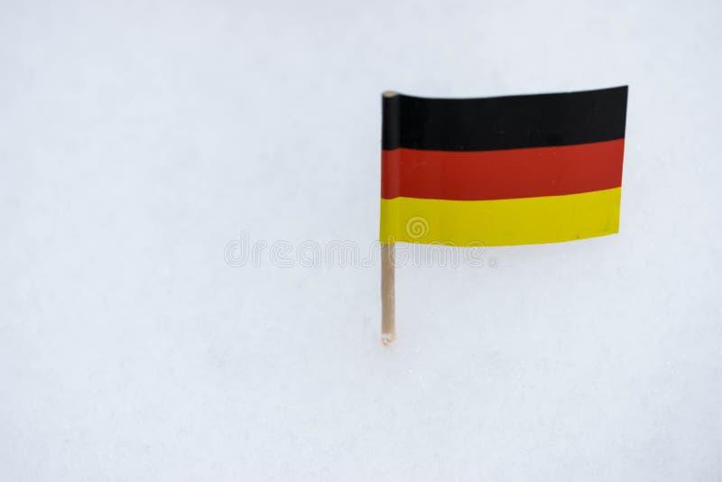 Η μικρή σημαία της Γερμανίας έκανε από το έγγραφο με την καφετιά οδοντογλυφίδα στο άσπρο υπόβαθρο χιονιού στοκ εικόνα