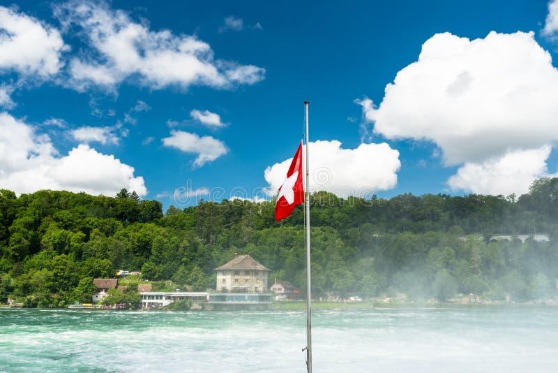 Η μισό-αναπτυγμένη σημαία της Ελβετίας που κρεμά στον ιστό, στο μπλε ουρανό υποβάθρου με τα άσπρα σύννεφα, τον ποταμό Ρήνος και τ στοκ εικόνες