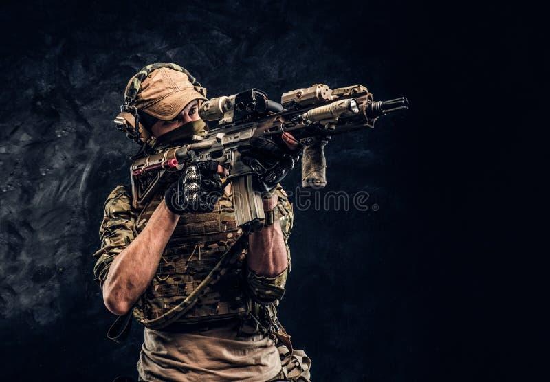Η μονάδα ελίτ, στρατιώτης ειδικών δυνάμεων στην ομοιόμορφη εκμετάλλευση κάλυψης ένα επιθετικό τουφέκι με μια θέα λέιζερ και στόχο στοκ φωτογραφία με δικαίωμα ελεύθερης χρήσης