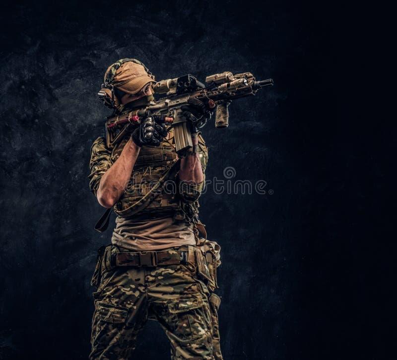 Η μονάδα ελίτ, στρατιώτης ειδικών δυνάμεων στην ομοιόμορφη εκμετάλλευση κάλυψης ένα επιθετικό τουφέκι με μια θέα λέιζερ και στόχο στοκ φωτογραφίες