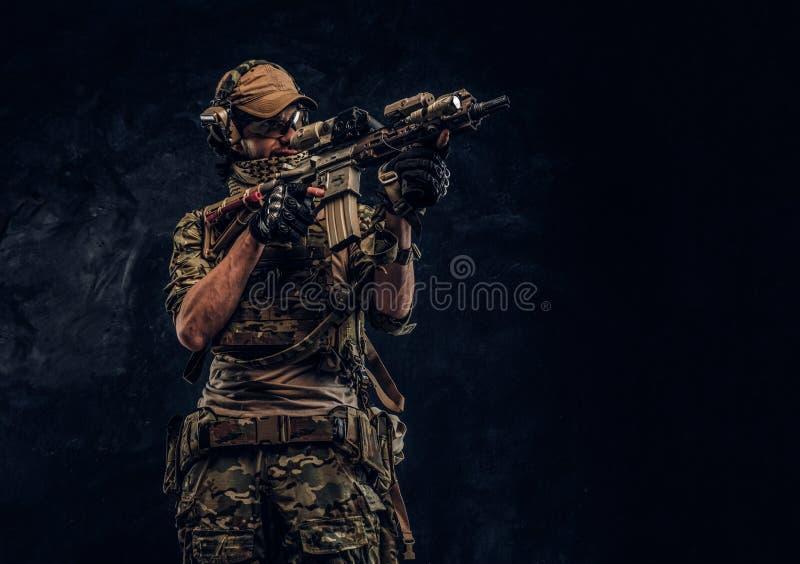 Η μονάδα ελίτ, στρατιώτης ειδικών δυνάμεων στην ομοιόμορφη εκμετάλλευση κάλυψης ένα επιθετικό τουφέκι με μια θέα λέιζερ και στόχο στοκ εικόνες