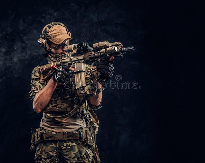 Η μονάδα ελίτ, στρατιώτης ειδικών δυνάμεων στην ομοιόμορφη εκμετάλλευση κάλυψης ένα επιθετικό τουφέκι με μια θέα λέιζερ και στόχο στοκ φωτογραφία