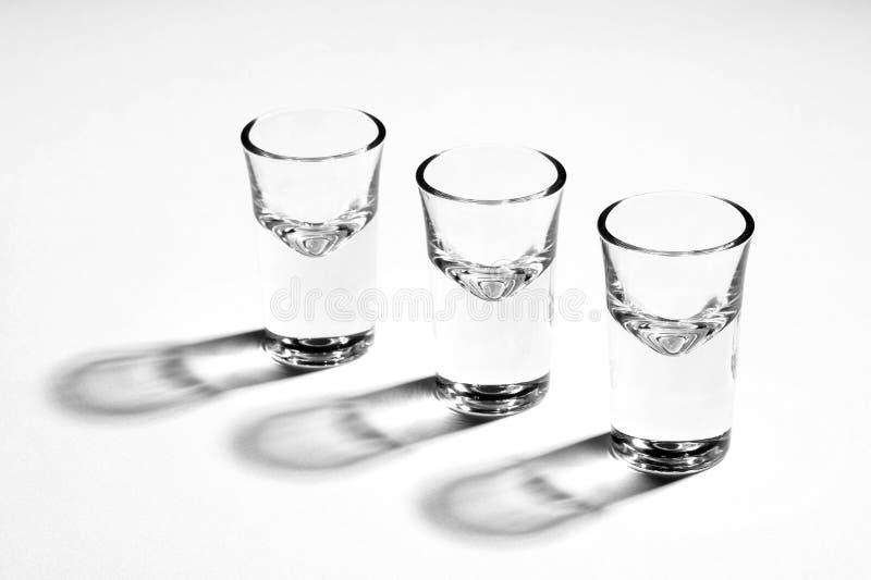 Η μονοχρωματική εικόνα τριών κενών πυροβοληθε'ντων γυαλιών, πλάτη άναψε, σκληρές αντανακλάσεις στοκ εικόνες