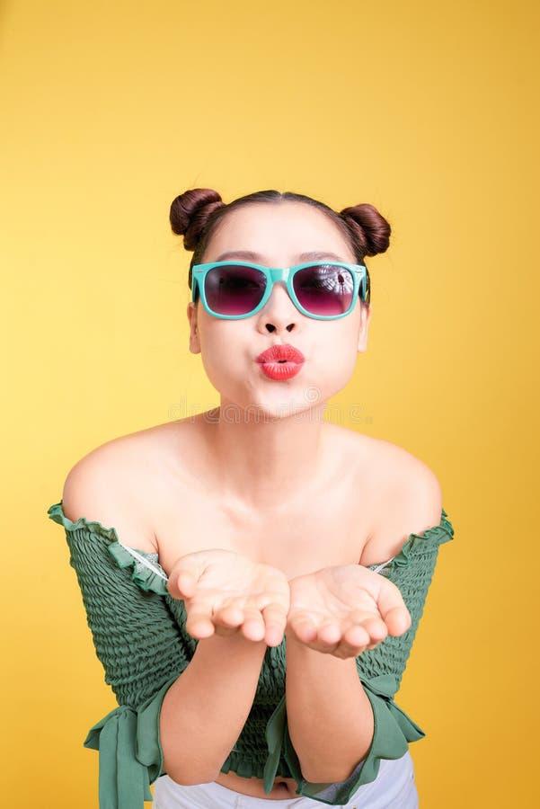 Η μοντέρνη ασιατική γυναίκα στα καθιερώνοντα τη μόδα γυαλιά ηλίου στέλνει ένα φιλί agains στοκ εικόνες με δικαίωμα ελεύθερης χρήσης