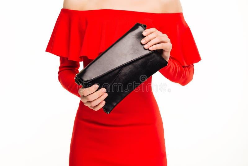 Η μοντέρνη γυναίκα με έναν μαύρο συμπλέκτη στα χέρια της και το κόκκινο βράδυ ντύνουν στοκ φωτογραφία με δικαίωμα ελεύθερης χρήσης
