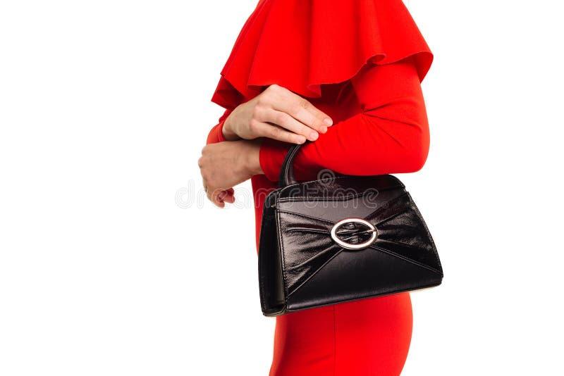 Η μοντέρνη γυναίκα με μια μαύρη τσάντα στα χέρια της και το κόκκινο βράδυ ντύνουν στοκ φωτογραφία