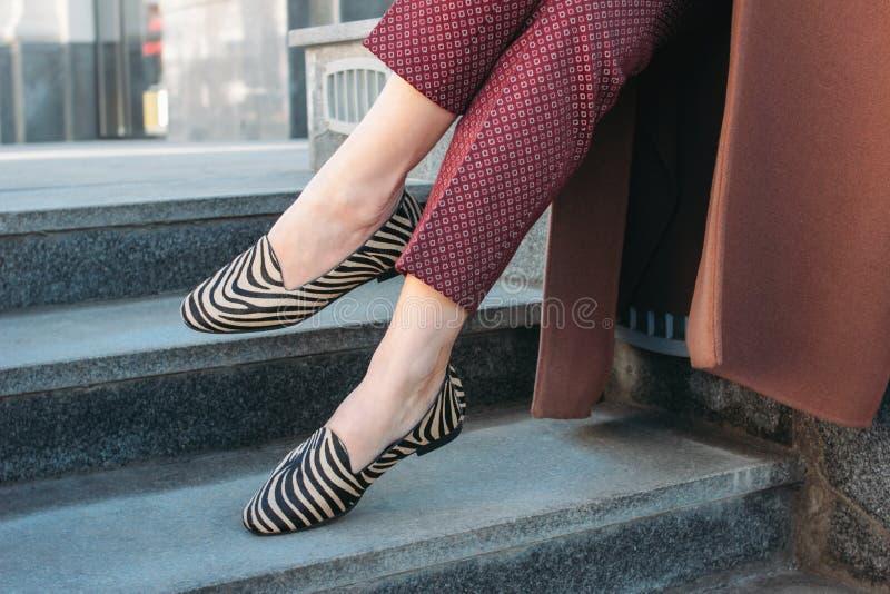 Η μοντέρνη μοντέρνη γυναίκα που φορά το μπεζ παλτό και Burgundy ασθμαίνει στα παπούτσια δέρματος πόνι στοκ εικόνες