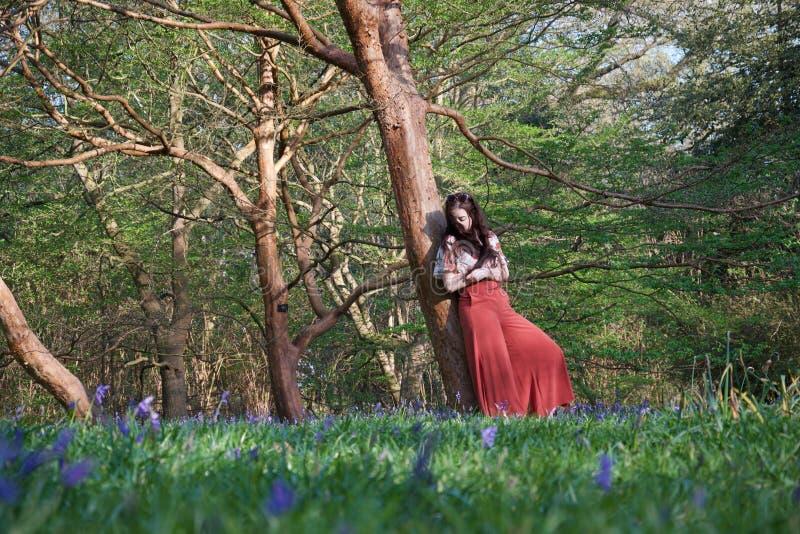 Η μοντέρνη κυρία κλίνει ενάντια σε ένα δέντρο σε μια αγγλική δασώδη περιοχή την πρώιμη άνοιξη, με τα bluebells στο πρώτο πλάνο στοκ εικόνες
