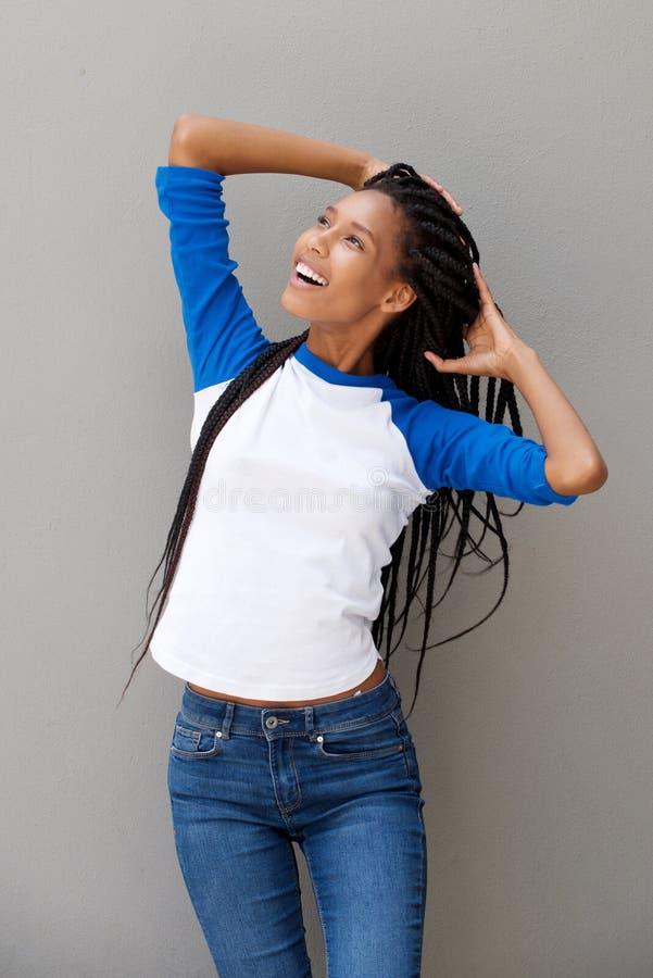 Η μοντέρνη νέα αφρικανική γυναίκα με παραδίδει την τρίχα κοιτάζοντας μακριά στοκ εικόνες