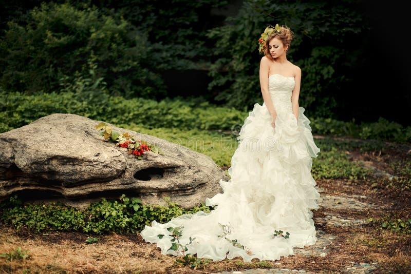 Η μοντέρνη νύφη σε ένα πολύβλαστο άσπρο φόρεμα υπερασπίζεται μια μεγάλη πέτρα στοκ φωτογραφίες