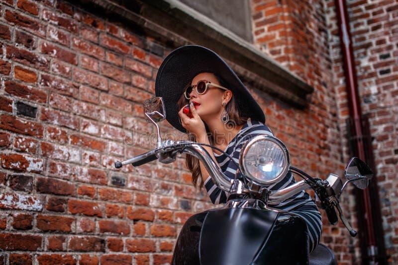 Η μοντέρνη φθορά γυναικών ντύνουν και η συνεδρίαση καπέλων που στέκεται δίπλα σε ένα μαύρο μηχανικό δίκυκλο και τα χρώματα τα χεί στοκ εικόνες