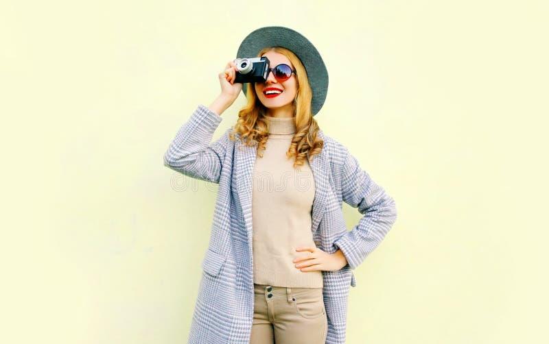Η μοντέρνη όμορφη χαμογελώντας γυναίκα κρατά την αναδρομική κάμερα που παίρνει την εικόνα στοκ φωτογραφία με δικαίωμα ελεύθερης χρήσης
