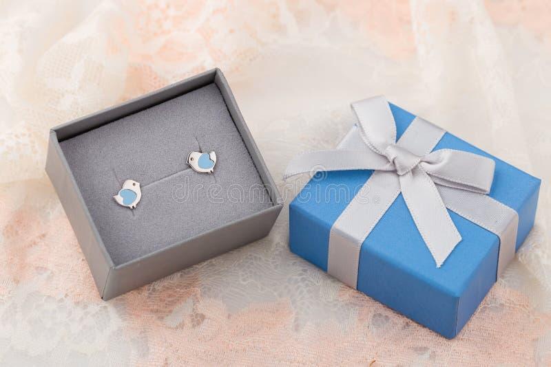 Η μορφή πουλιών με το μπλε σκουλαρίκι καρδιών στερεώνει στο κιβώτιο δώρων στην ΤΣΕ δαντελλών στοκ εικόνα