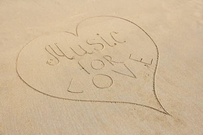 Η μουσική επιγραφής για την αγάπη επισύρεται την προσοχή στην άμμο και περιβάλλεται από την καρδιά Καρδιά στην άμμο στοκ φωτογραφία
