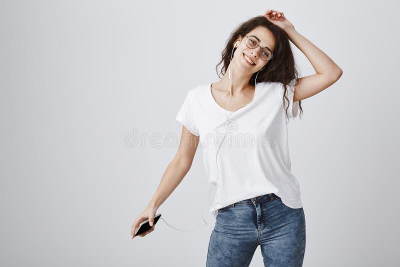 Η μουσική με παίρνει μακρυά από τα προβλήματα Πορτρέτο του έξυπνου ευτυχούς ελκυστικού κοριτσιού με τη σγουρή τρίχα που χορεύει,  στοκ εικόνες