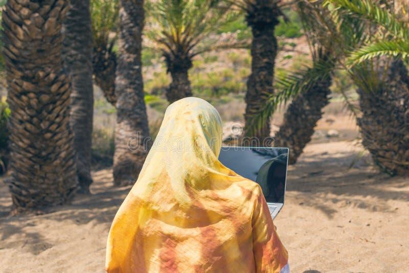 Η μουσουλμανική γυναίκα freelancer σε ένα ζωηρόχρωμο μαντίλι με το lap-top κάθεται στην παραλία Ντουμπάι Ταξίδι Halal στοκ εικόνα