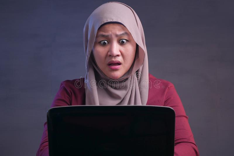 Η μουσουλμανική επιχειρηματίας που εργάζεται στο lap-top συγκλόνισε τη ζαλισμένη χειρονομία στοκ φωτογραφίες