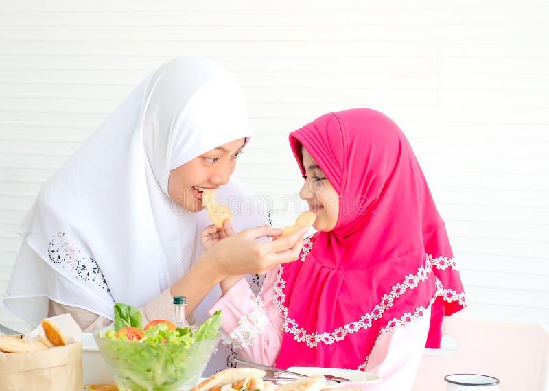 Η μουσουλμανική μητέρα και η κόρη της τρώνε τα μπισκότα μαζί με ένα κύπελλο της φυτικής σαλάτας στο άσπρο υπόβαθρο στοκ φωτογραφία με δικαίωμα ελεύθερης χρήσης