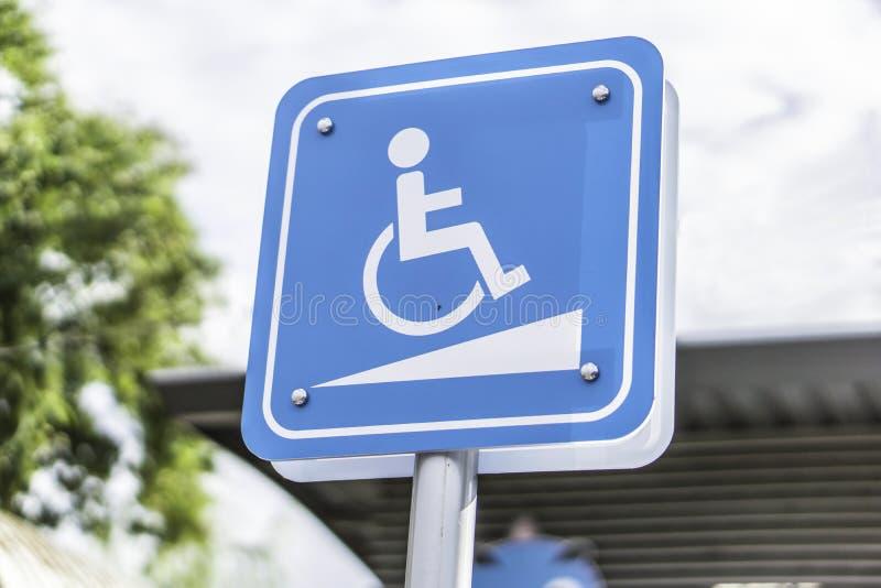 Η μπλε αναπηρία στο σημάδι αυτοκινήτων χώρων στάθμευσης υπαίθρια για τα άτομα με ειδικές ανάγκες, την αναπηρική καρέκλα ή παλαιότ στοκ εικόνα