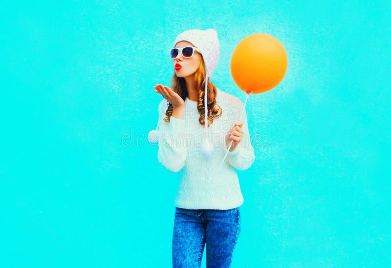 Η μόδα που η νέα γυναίκα στέλνει ένα φιλί αέρα κρατά το μπαλόνι στο άσπρο καπέλο στοκ φωτογραφία με δικαίωμα ελεύθερης χρήσης