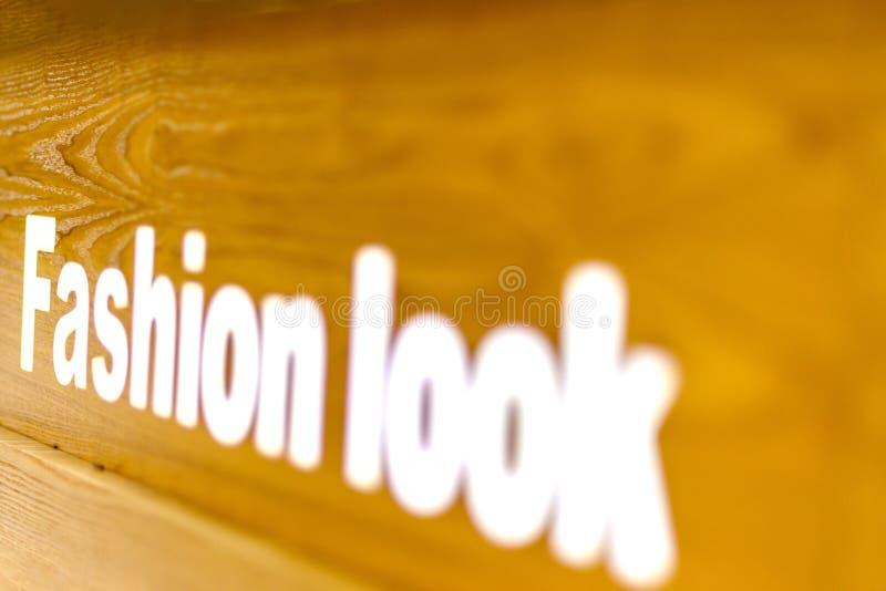 Η μόδα φαίνεται κείμενο λέξης που γράφεται επάνω στο ξύλινο υπόβαθρο, αναφέρει, υπογράφει, εγγραφή, έννοια, θολωμένο υπόβαθρο στοκ εικόνες με δικαίωμα ελεύθερης χρήσης