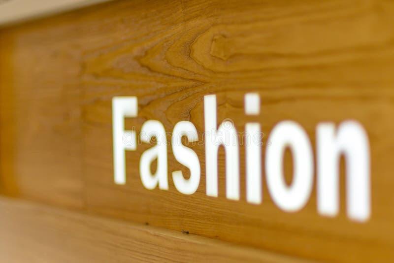 Η μόδα φαίνεται κείμενο λέξης που γράφεται επάνω στο ξύλινο υπόβαθρο, αναφέρει, υπογράφει, εγγραφή, έννοια, θολωμένο υπόβαθρο στοκ φωτογραφία με δικαίωμα ελεύθερης χρήσης
