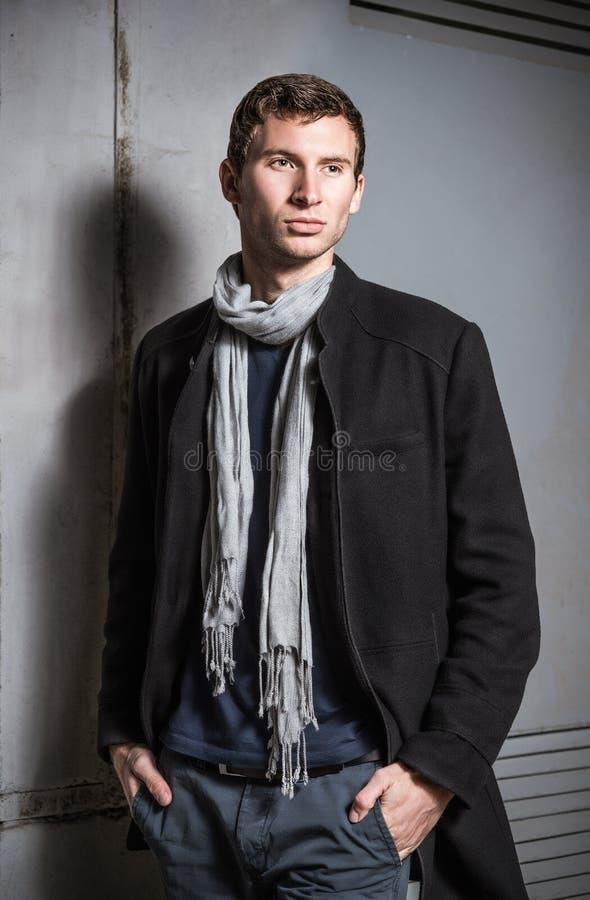 Η μόδα πυροβόλησε: πορτρέτο ενός όμορφου νεαρού άνδρα που φορά τα τζιν και το παλτό στοκ εικόνα