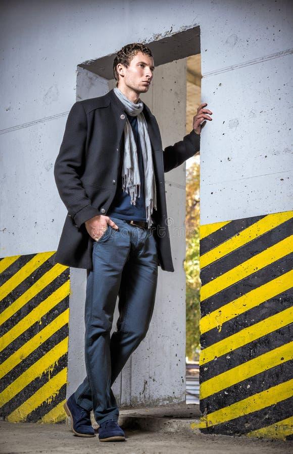 Η μόδα πυροβόλησε: όμορφος νεαρός άνδρας που φορά τα τζιν και το παλτό στοκ εικόνες