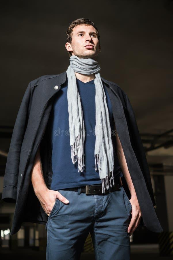 Η μόδα πυροβόλησε: όμορφος νεαρός άνδρας που φορά τα τζιν, το παλτό, το πουκάμισο και το μαντίλι στοκ εικόνες