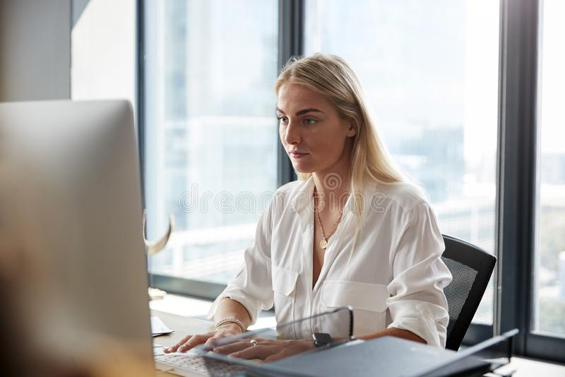 Η νέα άσπρη ξανθή συνεδρίαση γυναικών σε ένα γραφείο που λειτουργεί σε έναν υπολογιστή σε ένα δημιουργικό γραφείο, κλείνει επάνω στοκ φωτογραφία με δικαίωμα ελεύθερης χρήσης