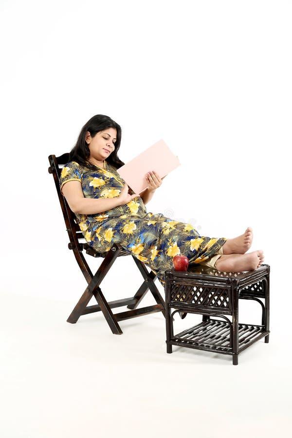 Η νέα έγκυος γυναίκα διαβάζει το περιοδικό μωρών με το κάθισμα στην καρέκλα στοκ φωτογραφία με δικαίωμα ελεύθερης χρήσης