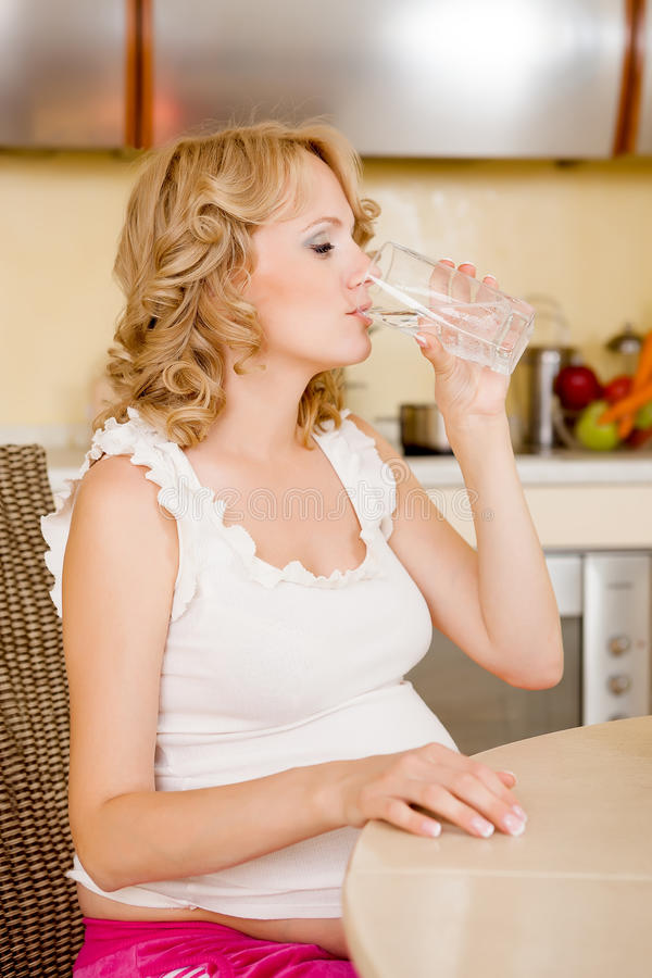 Η νέα έγκυος γυναίκα πίνει το νερό στοκ φωτογραφίες με δικαίωμα ελεύθερης χρήσης