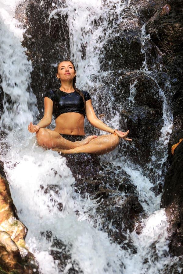 Η νέα απόλαυση γυναικών στη γιόγκα θέτει στον καταρράκτη στοκ εικόνα με δικαίωμα ελεύθερης χρήσης