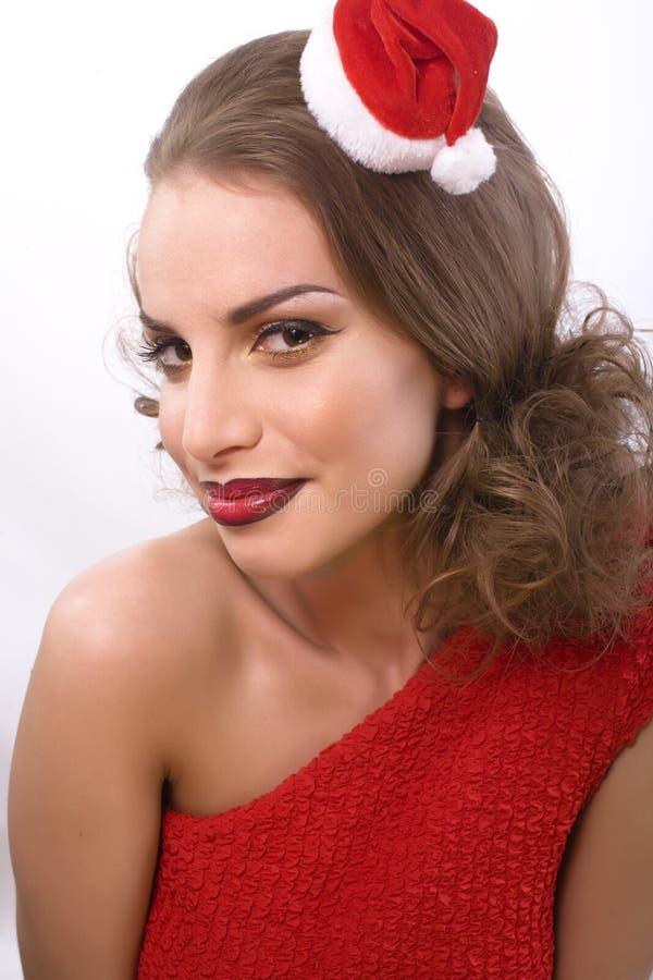 Η νέα αρκετά ευτυχής χαμογελώντας γυναίκα brunette στα Χριστούγεννα στο κόκκινο καπέλο santas απομόνωσε το δώρο καρδιών, έννοια α στοκ εικόνα
