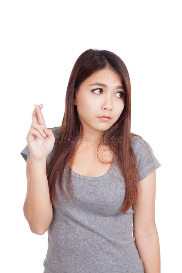 Η νέα ασιατική γυναίκα διασχίζει τα δάχτυλά της κοιτάζει μακριά στοκ φωτογραφία