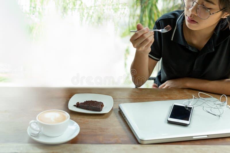 Η νέα ασιατική γυναίκα που έχει το διάλειμμα με brownie το κέικ στον καφέ επέλεξε την εστίαση στοκ εικόνες με δικαίωμα ελεύθερης χρήσης