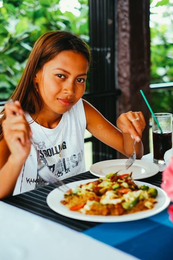 Η νέα ασιατική γυναίκα στην κατανάλωση εστιατορίων ανακατώνει το νουντλς ρυζιού τηγανητών με το κρέας και τα λαχανικά, φιλιππινέζ στοκ εικόνα