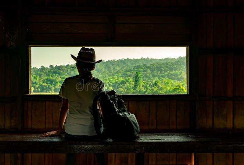 Η νέα ασιατική γυναίκα φορά το καπέλο κάθεται στην ξύλινη όμορφη άποψη πάγκων και προσοχής του τροπικού δάσους στον πύργο παρατήρ στοκ φωτογραφία