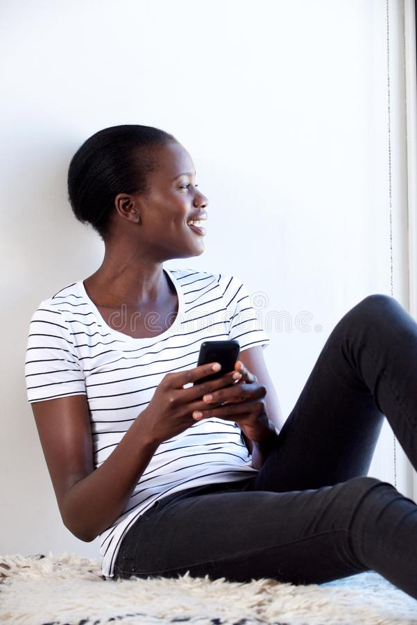 Η νέα αφρικανική συνεδρίαση γυναικών χαλάρωσε στο σπίτι με το κινητό τηλέφωνο στοκ εικόνα