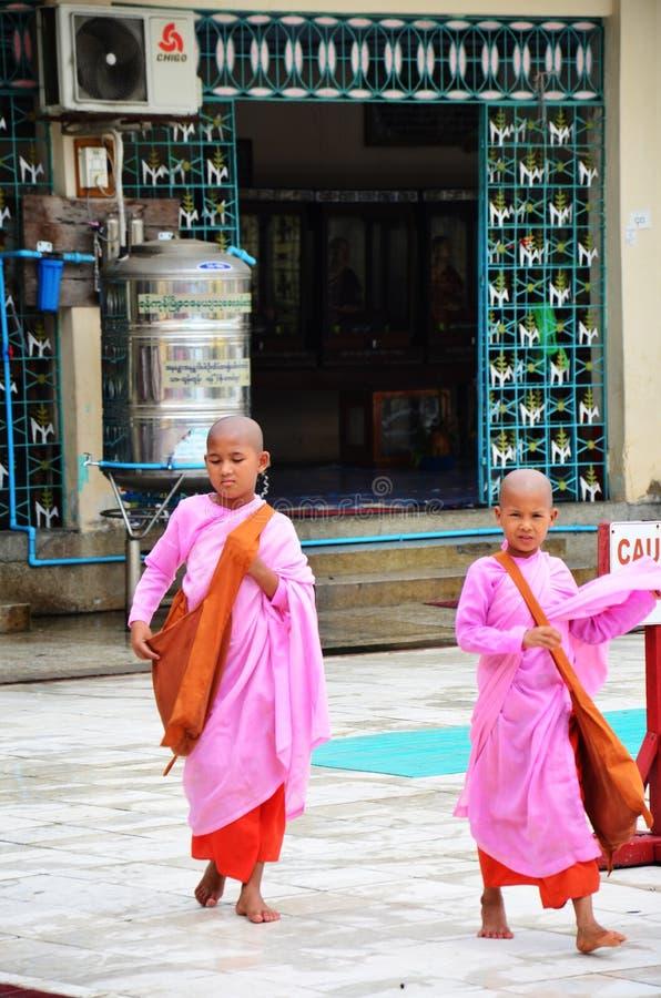 Η νέα βουδιστική γυναίκα ασκητική ή η καλόγρια που περπατά πηγαίνει να μελετήσει στην παγόδα Botahtaung στοκ εικόνες