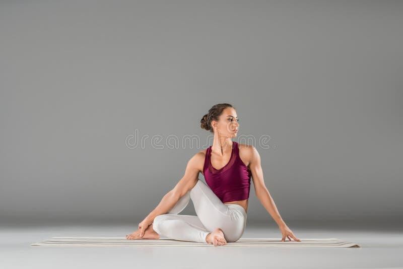 η νέα γιόγκα άσκησης γυναικών, που κάθεται στο μισό Λόρδο των ψαριών ασκεί, Ardha στοκ φωτογραφία