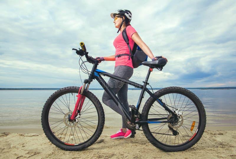 η νέα γυναίκα, ένας αθλητής στα ρόδινα παπούτσια, περπατά με ένα ποδήλατο βουνών στοκ φωτογραφίες