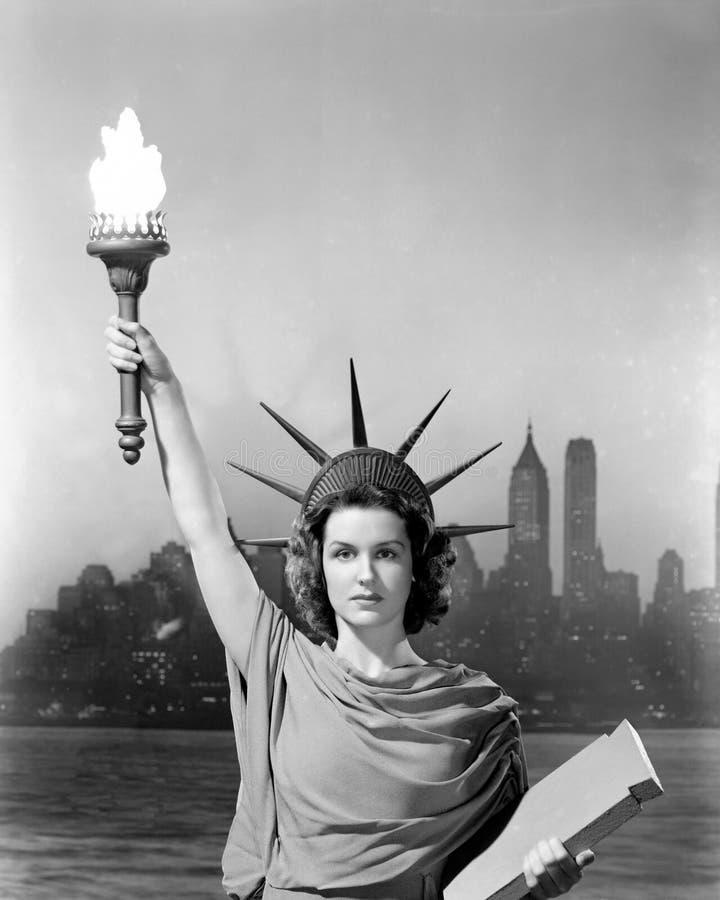 Η νέα γυναίκα έντυσε ως άγαλμα της ελευθερίας με τους ουρανοξύστες στο υπόβαθρο (όλα τα πρόσωπα που απεικονίζονται δεν ζουν περισ στοκ εικόνες