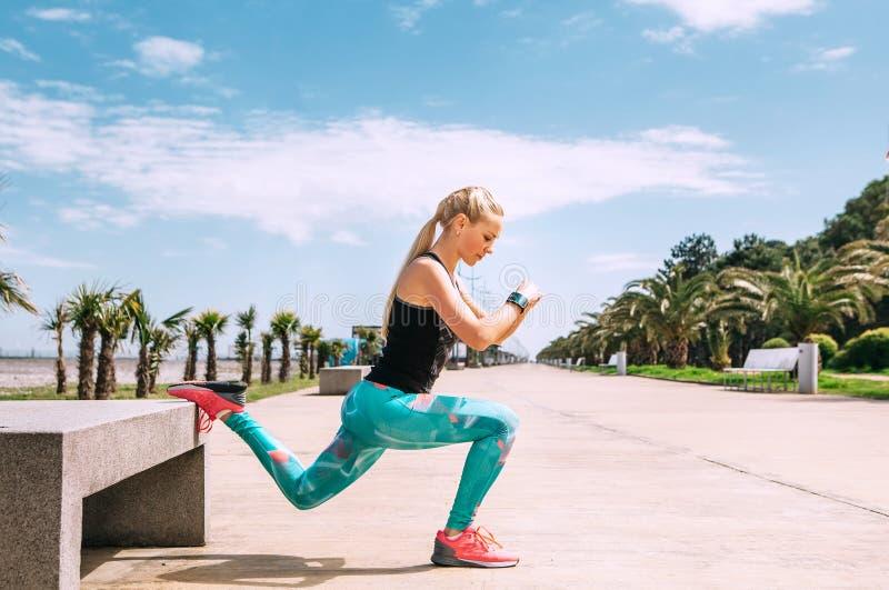 Η νέα γυναίκα έχει ένα υπαίθριο workout στο ανάχωμα θάλασσας στοκ εικόνες