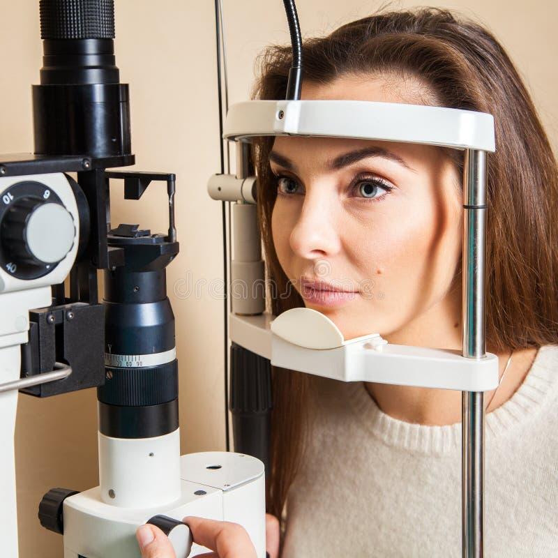Η νέα γυναίκα έχει την εξέταση οφθαλμών που εκτελείται από το γιατρό ματιών στοκ φωτογραφία
