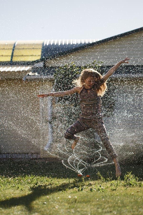 Η νέα γυναίκα έχει τη διασκέδαση με έναν ψεκασμό του νερού στοκ φωτογραφία