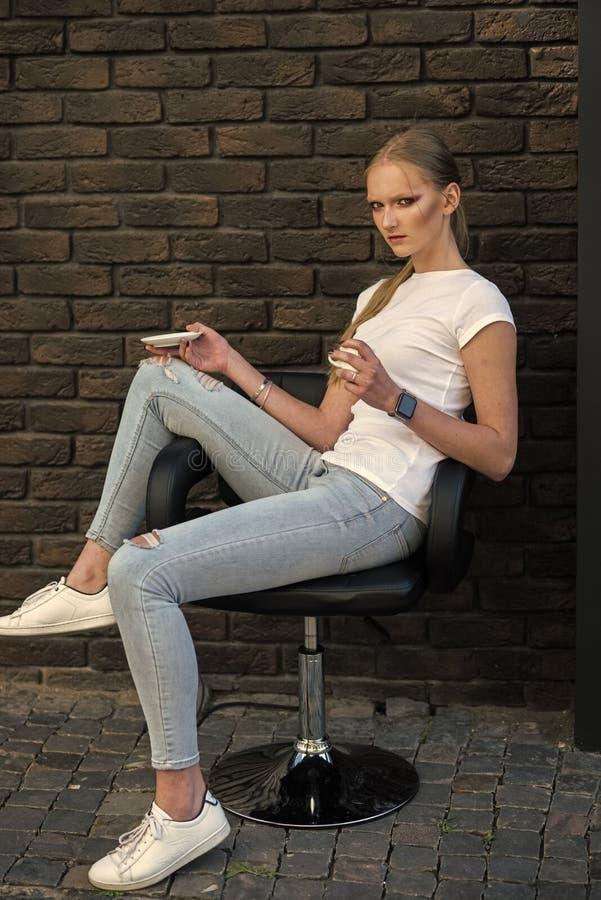 Η νέα γυναίκα έχει το διάλειμμα, διάθεση Το πρότυπο μόδας στο περιστασιακό ύφος χαλαρώνει στην πολυθρόνα Γυναίκα με το makeup στο στοκ εικόνα